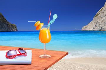 Orange cocktail on a beach table at Navagio beach on Zakynthos i