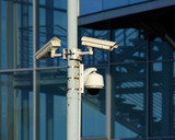 cctv cameras on front of modern glass building poster