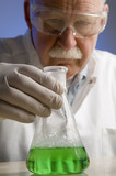 Chemist looking closely at his latest discovery poster