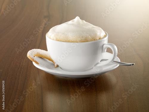Cappuccino mit Gebäck und Löffel