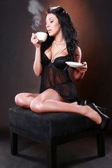 Hot brunette enjoys a cup of coffee