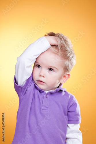 Disturbed little boy holding head with hand