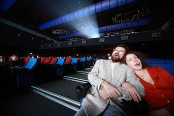 couples sit  in cinema and hug and look enthusiastically