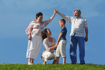 mother and son holding for hands, grandparents making house roof