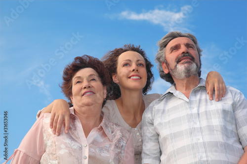 family of adult woman and parents embracing and smiling