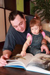father and little daughter in denim jumpsuit reads book
