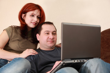 wife and husband sit on sofa and looking at laptop