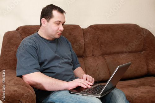 man sitting on sofa and working at laptop at home