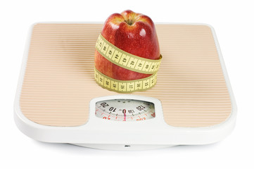 Scale, tape and apple on white