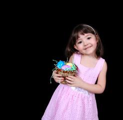 girl holding basket of bright easter eggs isolated on black