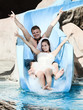 Groom and bride riding a water slide
