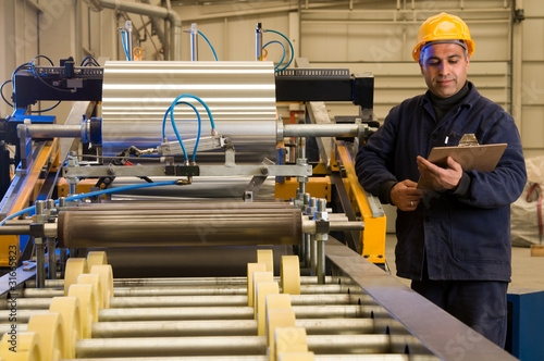 Factory worker processing roll of steel sheet.