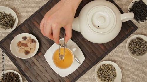 Woman adds brown sugar in cup of tea
