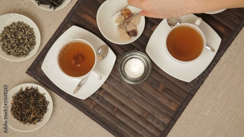 Woman adds brown sugar in cups of tea