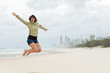 young woman jumps on the beach with joyful scream
