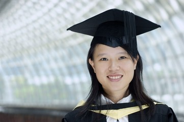 Smiling asian chinese lady graduate indoors