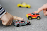 Innocence, childhood concept - playing with toy car poster