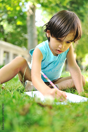 Young boy outdoors on the grass writing