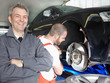 Master mechanic is happy with his job in a garage