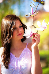 Outdoor portrait of attractive young woman with flower