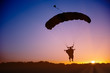 Skydiver silhouette under parachute in wingsuit against sunset