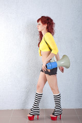sexy young red-haired woman with megaphone
