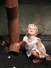 Toddler girl and rainwater pipe