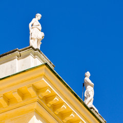 two baroque statues atop a rooftop