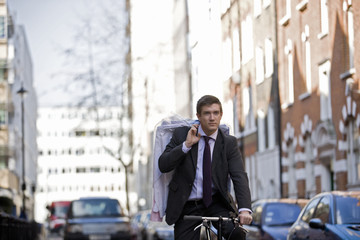 A businessman on his bicycle, carrying his dry cleaning