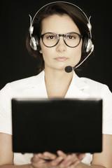 Frau mit Laptop und Kopfhörer