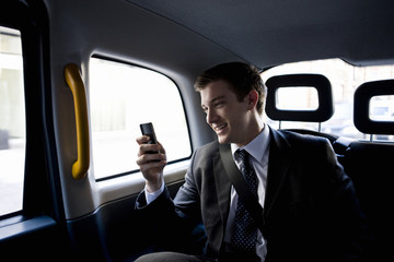 A businessman in a taxi, using his mobile phone