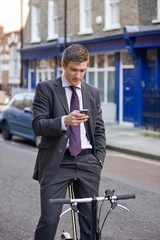 A businessman on his bicycle, looking his phone
