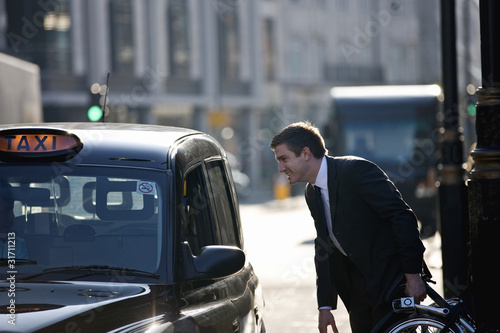 A businessman with his folded bicycle, talking to a taxi driver
