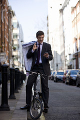 A businessman on his bicycle, looking at his phone