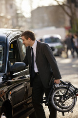 A businessman talking to a taxi driver, carrying folded bicycle