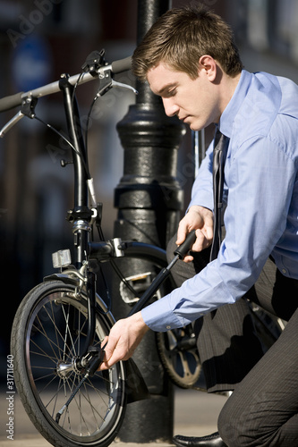 A businessman pumping up the tires on his bicycle