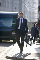 A businessman carrying his folded bicycle along the street