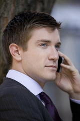 Portrait of a businessman using his mobile phone, outside