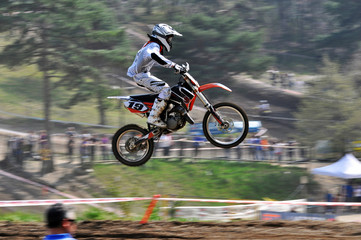 Motorcyclist while performing a jump with his bike