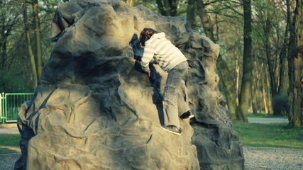Young boy climbing a rock in the park