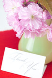 sakura flower in a vase and a card signed thank you on a red bac