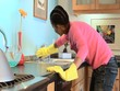 Young African American woman cleaning countertop in kitchen