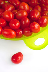 Red tomatoes in the  green colander.