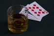 Glass with cognac and playing cards