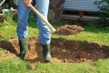 Mann schaufelt Erde aus einer Grube