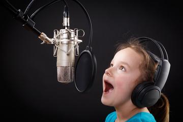 kleines mädchen singt in ein mikrofon
