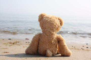 Teddybär einsam am Strand - Symbol für Single-Urlaub, etc.