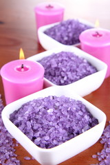 Lavender spa salt and lavender candles on a wooden background