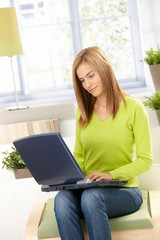 Young woman in green using laptop at home