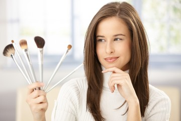 Pretty woman with makeup brush set